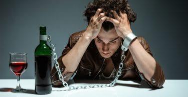 Homem com os cotovelos apoiados numa mesa, e sua testa está apoiada em suas mãos. Grilhões prendem seu braço esquerdo a uma garrafa de vinho, que está em cima da mesa, com uma taça de vinho cheia ao lado.