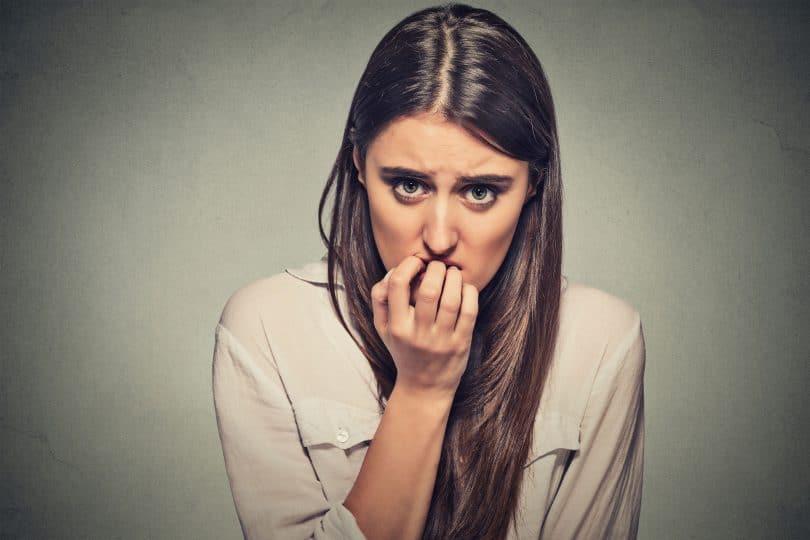Mulher com a mão na boca com expressão de medo