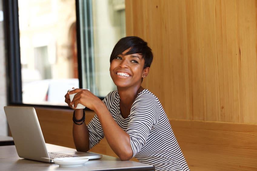 Mulher sorrindo com xícara de café na mão.