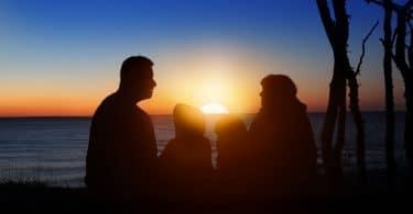 Silhueta de uma família em um pôr-do-sol.