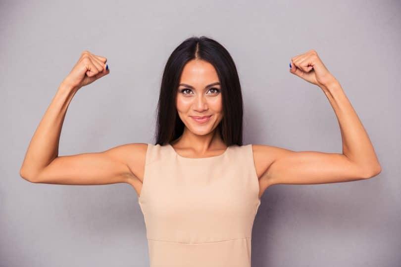 Mulher sorrindo com os braços para cima mostrando os bíceps