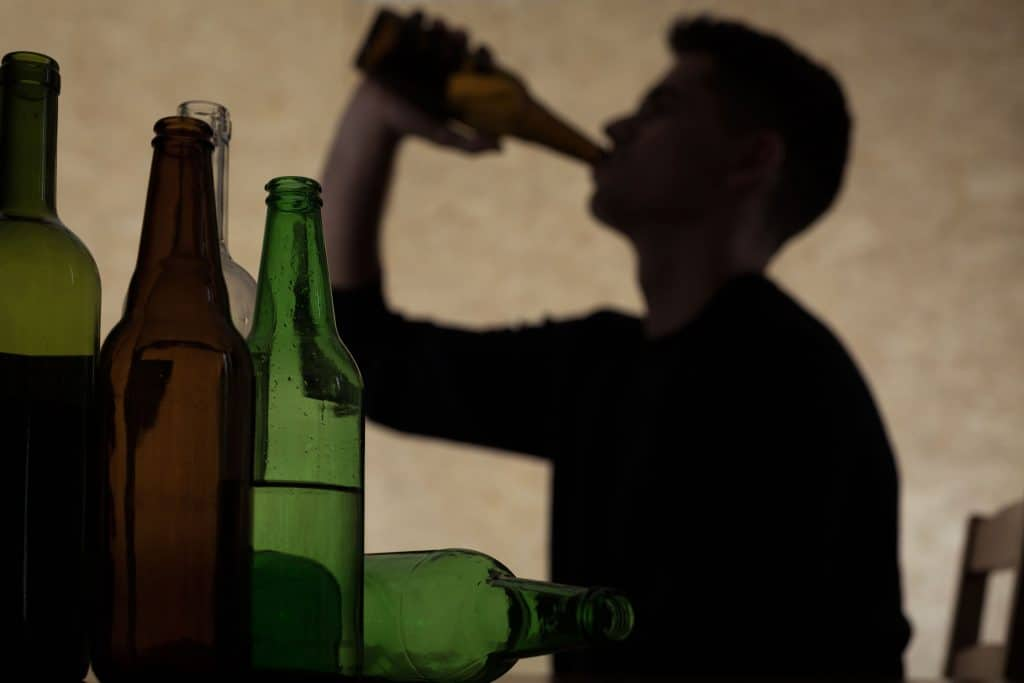 Sombra de homem jovem bebendo algo de uma garrafa de vidro, projetada em uma parede. Em foco na imagem, uma mesa com muitas garrafas verdes de vidro vazias
