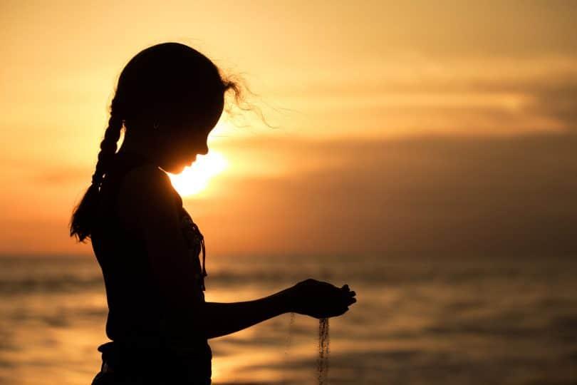Silhueta de menina em praia, com o pôr do sol ao fundo, segurando areia com as duas mãos, e a areia escapando entre seus dedos.