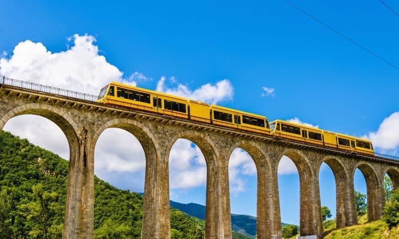 Trem amarelo passando pela ponte.