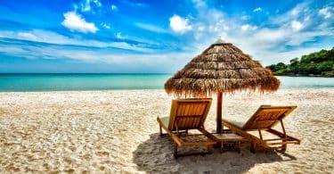 Duas espreguiçadeiras de praia sob a tenda na praia.