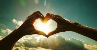Duas mãos fazendo o formato de coração para o céu, e o sol está dentro do coração.