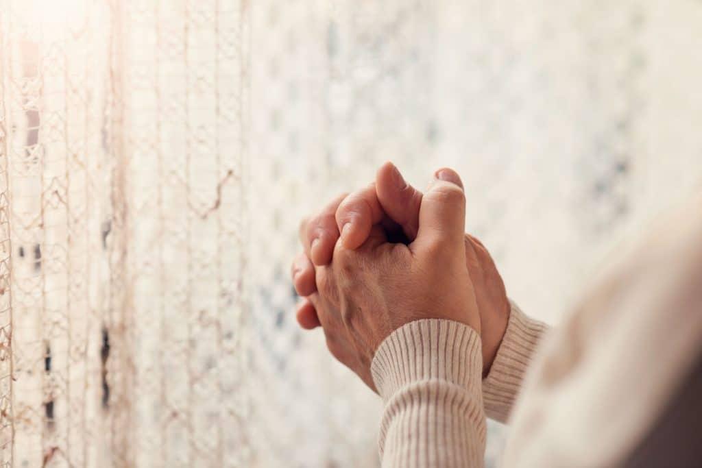 Mulher com as mãos juntas rezando ao lado da janela