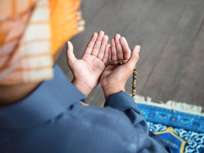 Pessoa com turbante ajoelhada em um tapete, com as mãos estendidas em sinal de oração.