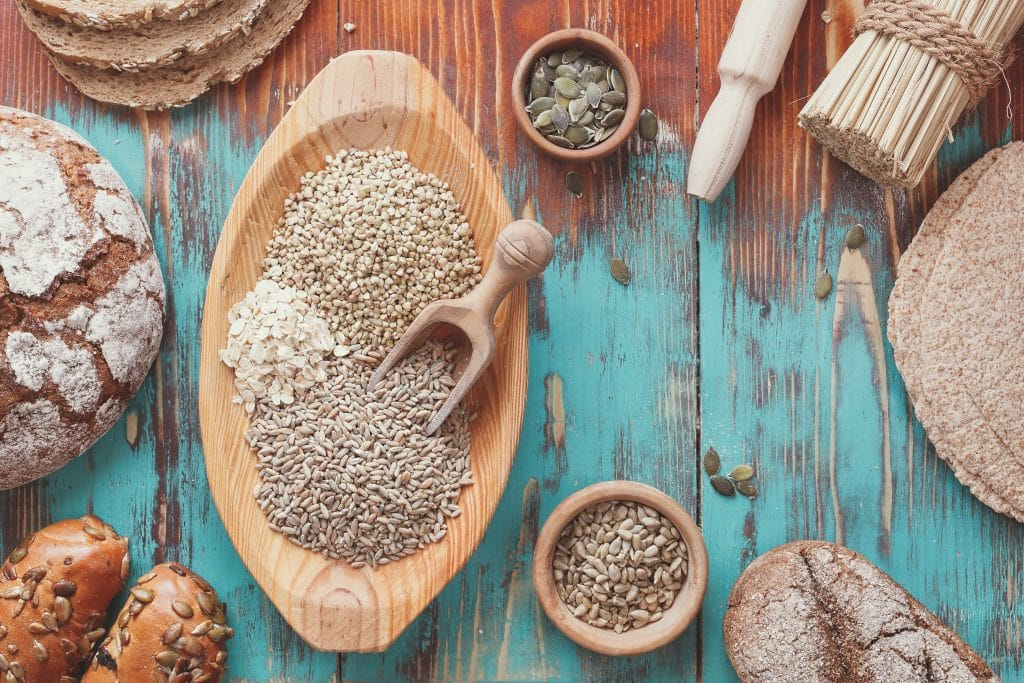 Grade travessa de madeira em formato oval com alguns cereais. Essa travessa está sobre uma mesa de madeira na cor azul. Ao temos alguns pães e outros tipos de grãos e cereais. Direitos autorais : Slasta.