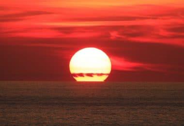 Sol grande por estar muito próximo da Terra, se pondo no horizonte do mar.