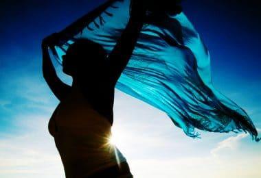 Silhueta de mulher segurando um pano azul.