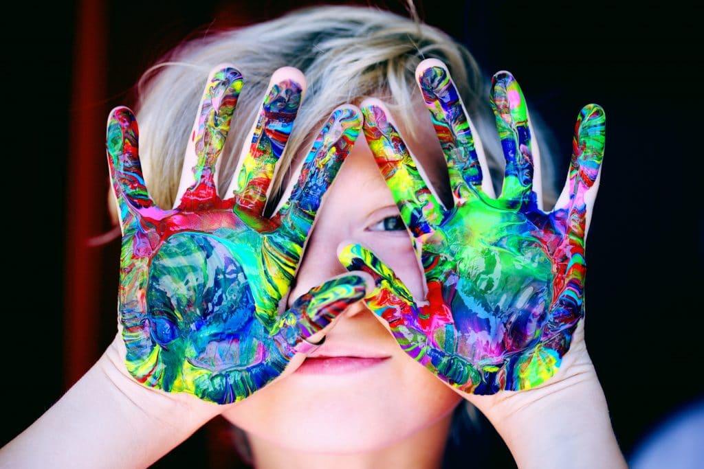 Criança com mãos sujas de tintas coloridas em frente ao rosto