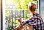 Mulher olhando para varanda enquanto segura uma xícara de café