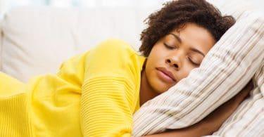 Mulher deitada na cama com os olhos fechados