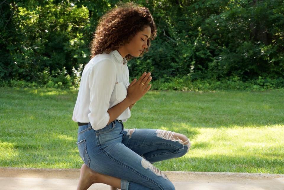 Mulher ajoelhada no chão rezando