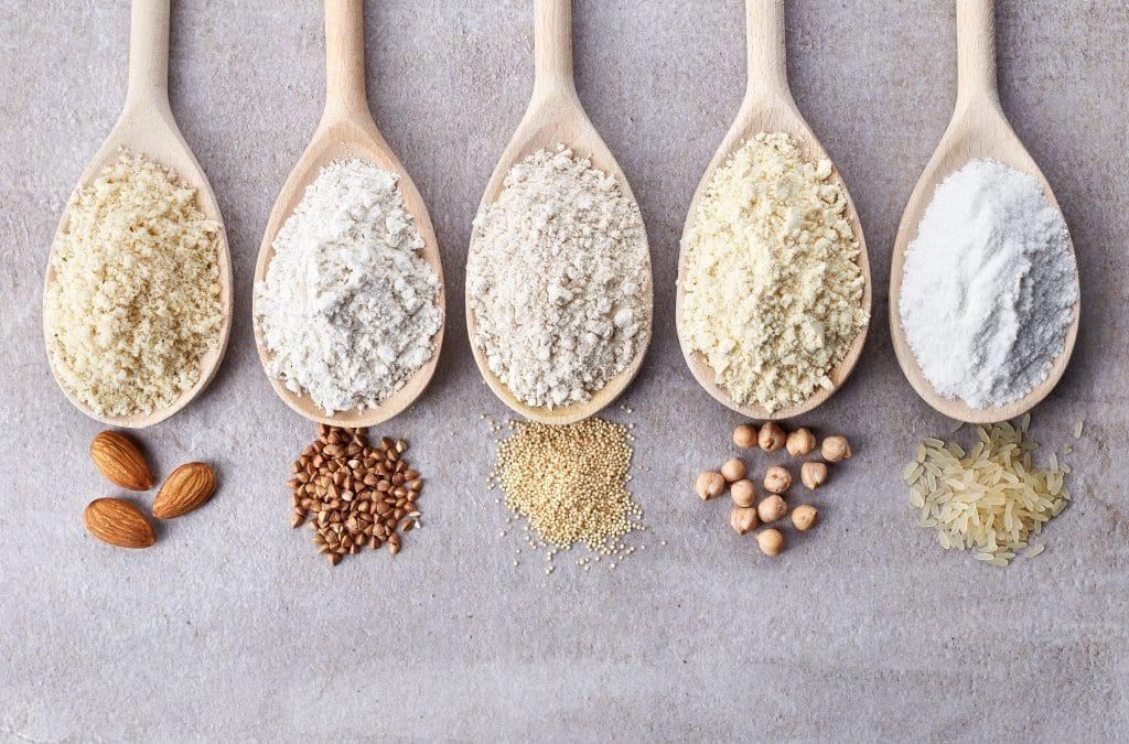 Cinco grandes colheres de madeira. Cada uma dela traz um tipo de farinha e na ponta de cada temos a referência do que é cada uma dessas farinhas, como amêndoa, arroz, soja, linhaça e aveia. Direitos autorais : Baiba Opule