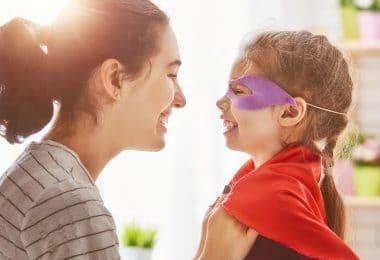 Mãe arrumando capa de super-herói da filha que está sorrindo