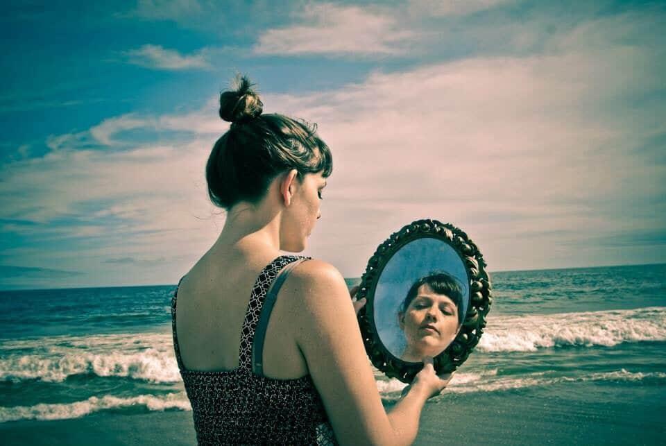 Mulher segurando espelho de frente para o mar
