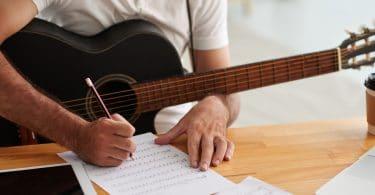 Homem sentado em uma mesa com um violão sobre o colo enquanto escreve músicas em uma folha.