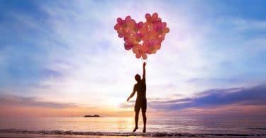 Silhueta de pessoa segurando balões formando um coração na praia