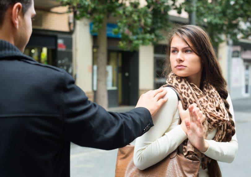 Homem seguindo mulher na rua e encostando em seu ombro. A mulher olha com para o homem incomodada, e estende sua mão para ele se distanciar.