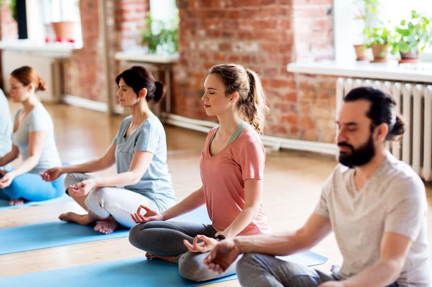Quatro pessoas meditando.