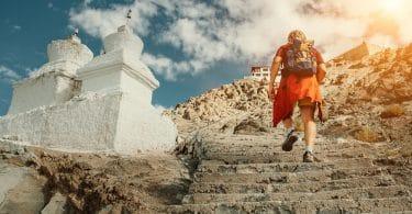 Homem subindo escadas entalhadas em uma montanha. Ao lado dele vemos duas torres brancas, e no topo da montanha, um templo sagrado.