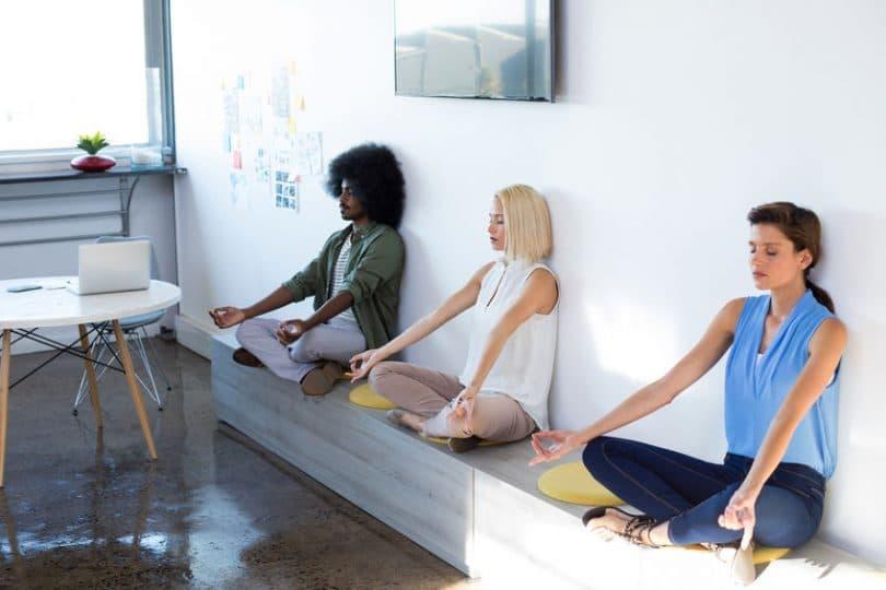 Três pessoas meditando em escritório.