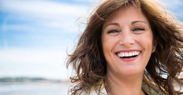 Mulher de meia-idade rindo, com os cabelos ao vento, em frente a um rio em um dia ensolarado.