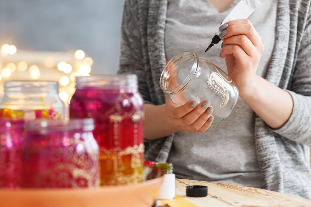 Mulher decorando jarras de vidro com tinta.