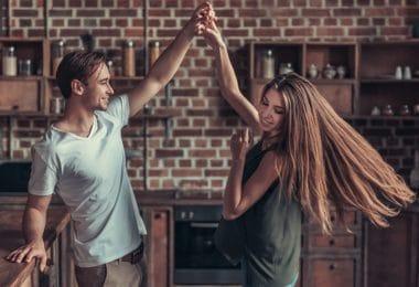 Casal jovem feliz dançando na cozinha