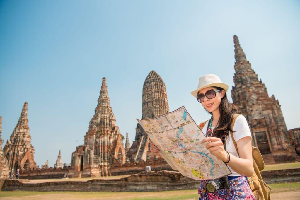 Mulher usando óculos escuros e chapéu, segurando e olhando para um mapa em suas mãos. Ao fundo, os monumentos da cidade de Ayutthaya.