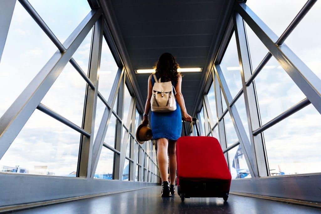Mulher de costas, puxando mala de rodinhas, em corredor que liga o portão de embarque à aeronave.