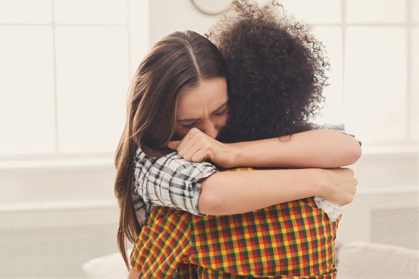 Duas moças se abraçando.