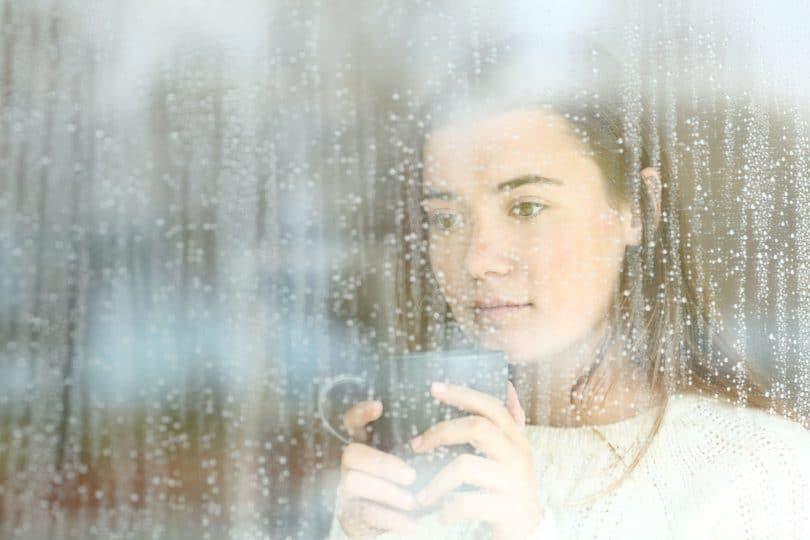 Mulher segurando caneca com as duas mãos e olhando através de janela, molhada do lado de fora pela chuva.