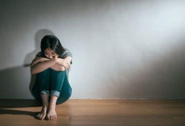Mulher jovem sentada no chão, abraçando suas pernas que estão flexionadas e com um olhar preocupado.