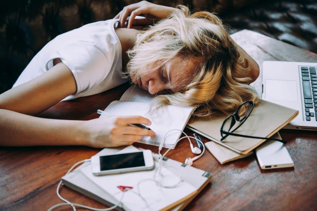 Mulher dormindo na mesa com cadernos e folhas espalhadas