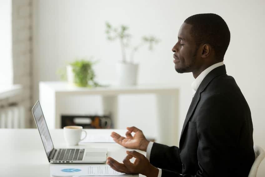 Homem meditando em mesa de trabalho.