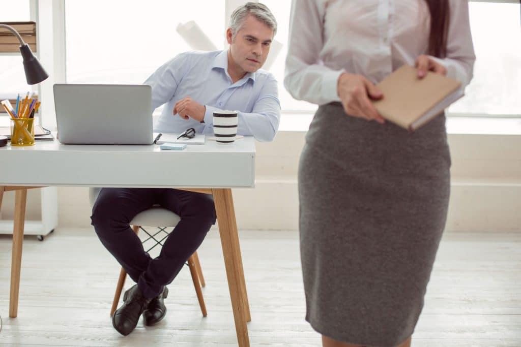 Mulher de pé em escritório, usando saia e camisa, segurnado uma agenda. Atrás dela, um  homem sentado se inclina para fora de sua mesa, para poder olhar o corpo da mulher.