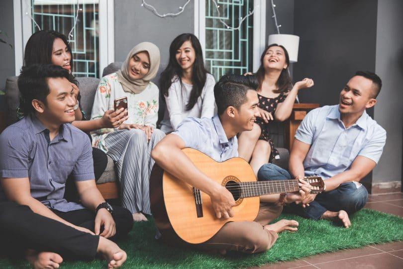 Grupo de sete amigos, onde quatro mulheres sentam em um banco, e três homens sentam no chão aos seus pés. O homem do meio toca violão, enquanto a mulher da ponta esquerda segura seu celular. Todos riem.