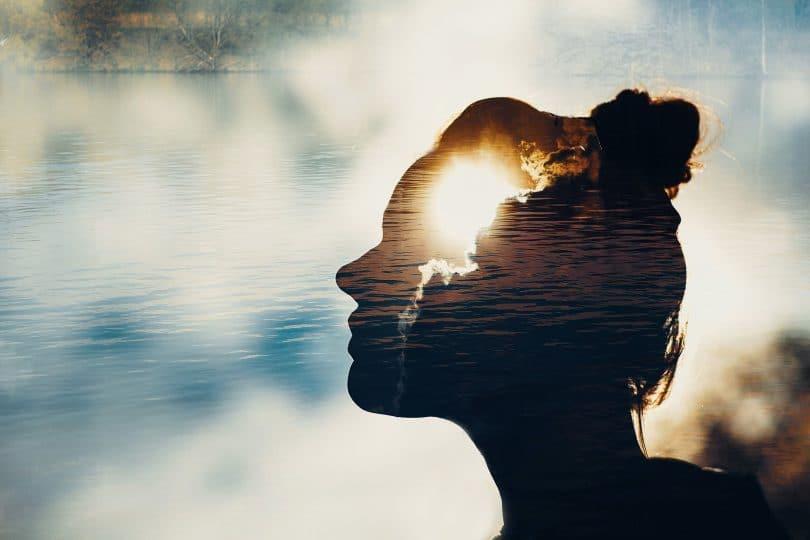 Rosto de uma mulher se fundindo com o céu e o sol