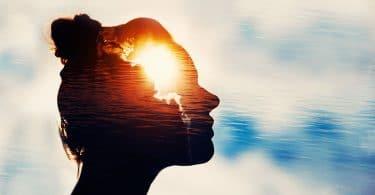 Silhueta de rosto feminino com imagem de luz dentro e céu com nuvens ao fundo