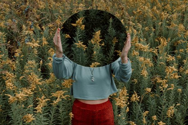 Mulher em um campo de flores segurando um espelho na frente da cabeça, a qual se torna invisível.