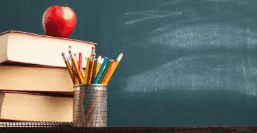 Livros de estudo, maçã e lápis de cor