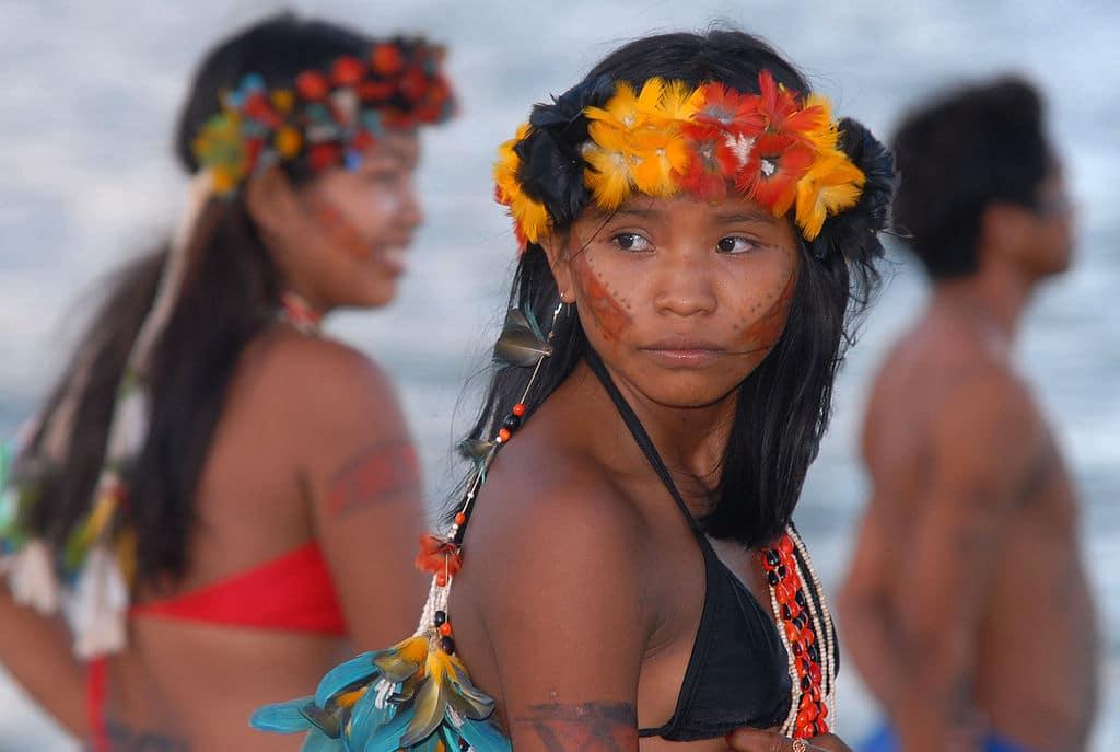 Menina da tribo Tapirajé, usando um ornamento de penas coloridas em laranja, vermelho e preto na cabeça, brinco de penas azuis, laranjas e amarelas, colares de sementes e pedras, e rosto pintado com duas faixas vermelhas.
