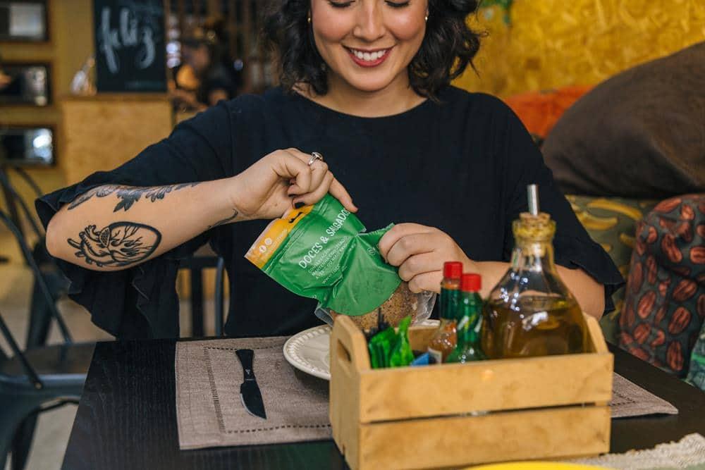 Mulher sorrindo ao abrir um pacote de comida congelada.