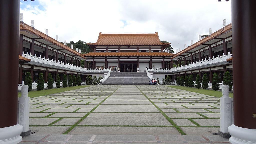 Imagem do Templo Zu Lai, onde nas laterais vemos corredores elevados, cobertos com telhado e grades brancas laterais, ao fundo o templo com colunas marrons e paredes brancas. Na frente dele, existe uma escada que leva a um espaço gramado com pedaços de piso cimentado.