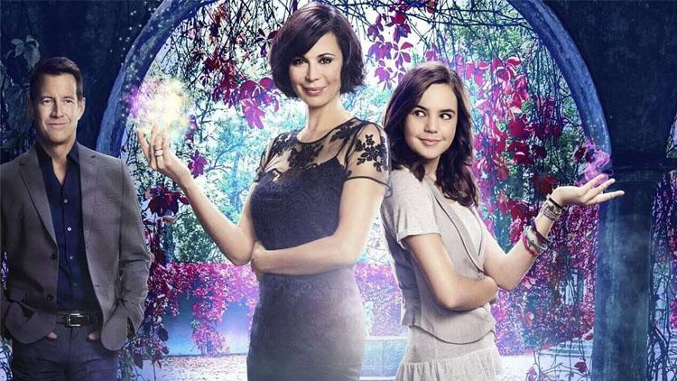 Duas mulheres com os ombros encostados e com as mãos apoiadas no braço com uma luz saindo e homem atrás olhando para elas.