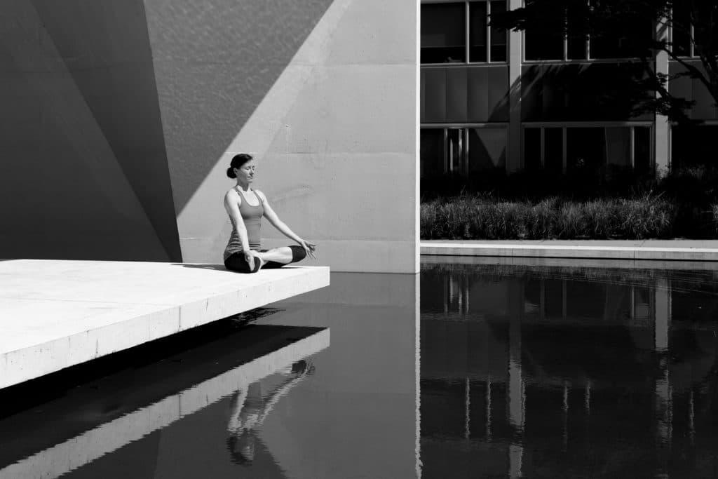 Mulher em posição de meditação  tomando sol em preto e branco