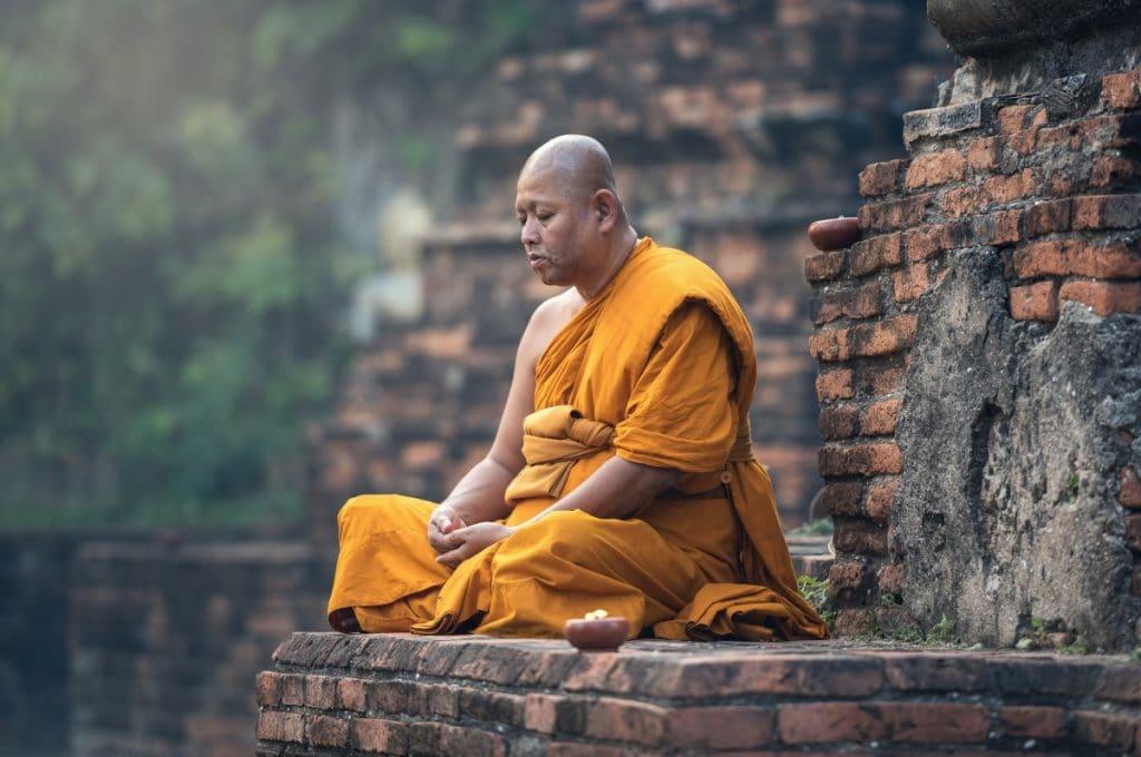 Monge budista meditando em construção antiga. Ele usa trajes típicos laranja, e seus olhos estão fechados.
